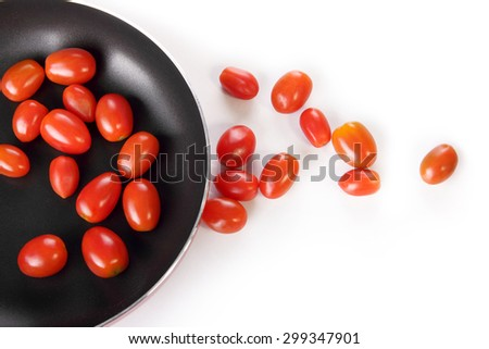 Composition of cherry tomatoes and frying pan, overhead shot isolated over white background - stock photo