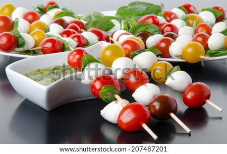 Composition of cherry tomatoes and mozzarella on skewers and a vinaigrette sauce with basil - stock photo