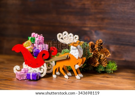 composition of Christmas decoration  reindeer and Santa sleigh with gifts, branch fir tree, pinecones on wooden background, closeup  - stock photo