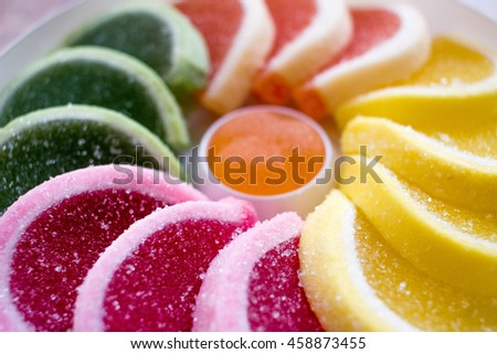 Composition of colorful jellies (green, orange, yellow, purple) in a shape of a half moon in a white box with one round jelly in the middle