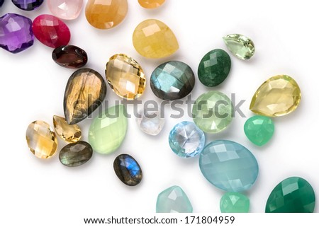Composition of colorful precious gems on the white background. Many different colors and shapes. Citrine, amethyst, ruby, emerald, blue topaz, labradorite, garnet, moonstone, rose quartz and more. - stock photo