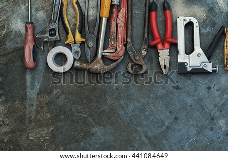Composition of construction tools on an old battered concrete surface consisting of insulating tape, pliers, pipe wrench, screwdriver, industrial stapler, hammer, metal shears - stock photo