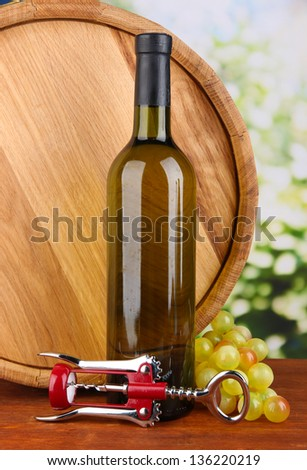 Composition of corkscrew and bottle of wine, grape, wooden barrel  on wooden table on bright background - stock photo