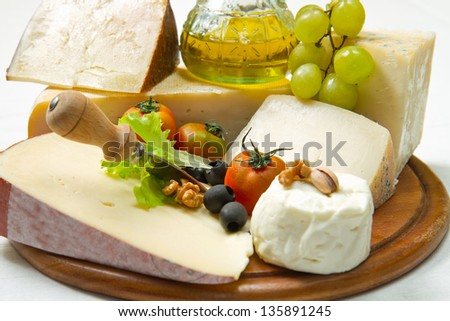 composition of different type of cheese on wooden board