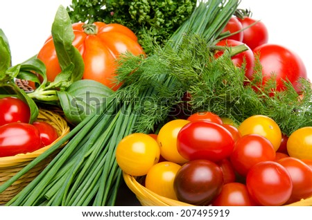Composition of different varieties of tomatoes in baskets with herbs