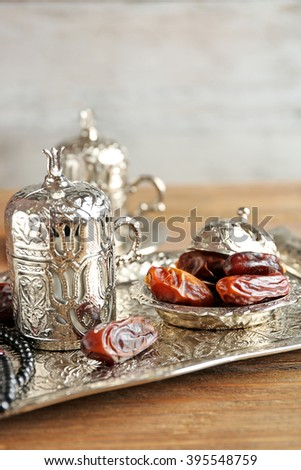 Composition of dried dates in holiday dish and rosary on wooden table - stock photo