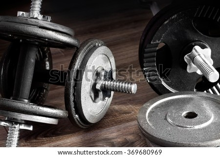 Composition of dumbbells and barbells on the wooden background