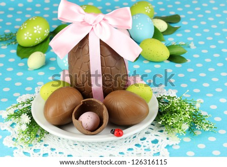 Composition of Easter and chocolate eggs on blue fabric background - stock photo