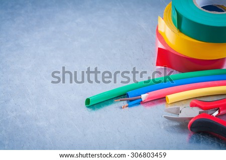 Composition of electric wire protection cables sharp nippers electricians tape. - stock photo