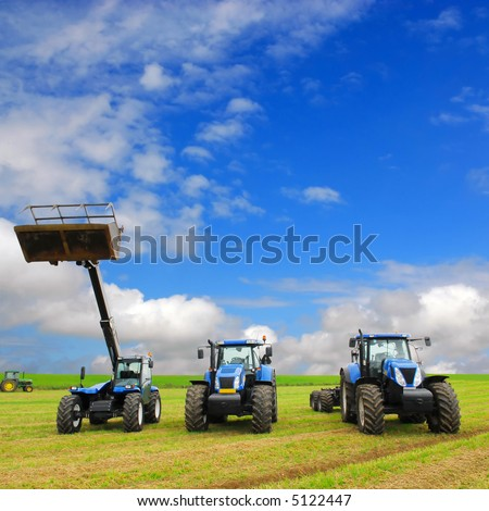 composition of farming machinery on farmland with blue sky background - stock photo