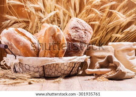 Composition of fresh bread, cereals and grains on wooden board. - stock photo