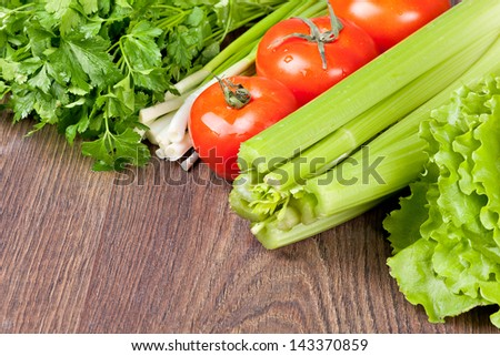 Composition of fresh vegetables on a wooden background