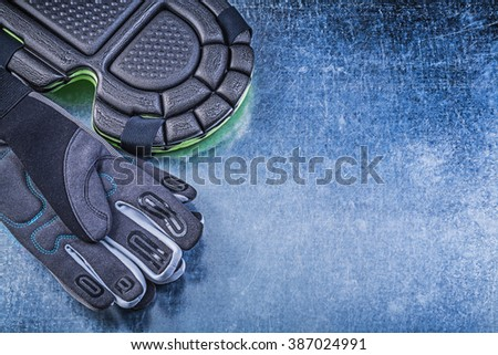 Composition of gardening safety gloves knee pads on metallic background agriculture concept. - stock photo