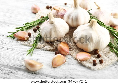Composition of garlic and rosemary on sacking, close up - stock photo