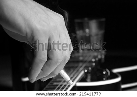 Composition of guitar and man's hand with cigarette smoking on black background