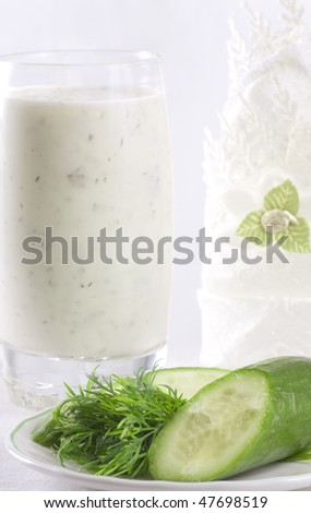 Composition of kefir in the glass with cucumber and dill near on the plate - stock photo