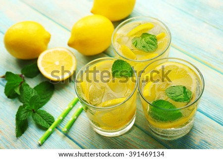 Composition of lemonades,  lemons and mint on blue wooden table background, closeup