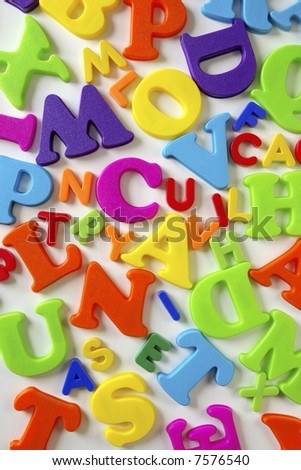 Composition of many colorful plastic toy letters over white background