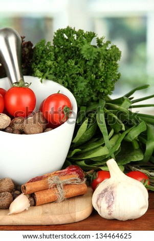 Composition of mortar, spices, tomatoes and  green herbs, on bright background