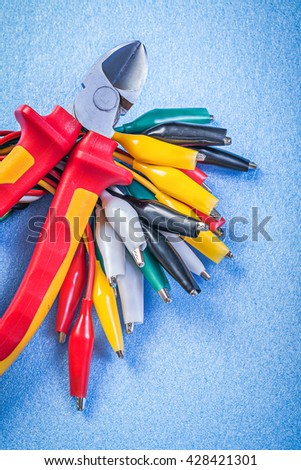 Composition of multicolored cable crocodiles nippers on blue background.