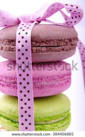 Composition of multicolored macaroon with a pink ribbon on a white background - stock photo