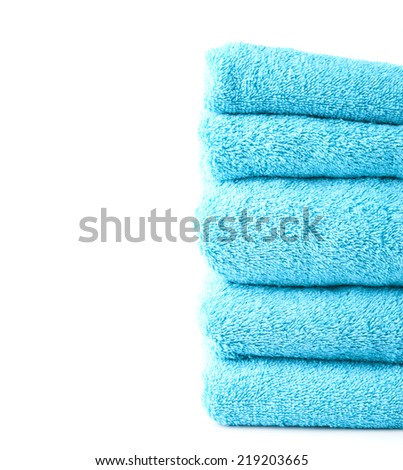 Composition of multiple blue terry cloth bath towels in a pile against the white background - stock photo
