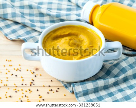 Composition of mustard and mustard seeds on wooden background. - stock photo