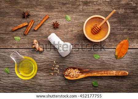 Composition of nature spa ingredients on the dark wooden table. Spa and wellness with honey ,herbal compress ball,turmeric,cinnamon powder ,cinnamon sticks ,aromatic oil and star anise. - stock photo