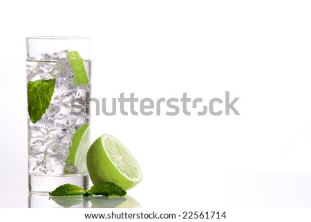 Composition of one mojito, one lime and  a mint leaf.