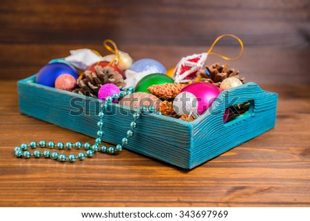 composition of retro wooden box with Christmas decoration, tinsel,  pinecones, stars, balls and beads on wooden background, closeup - stock photo