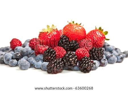 Composition of ripe black and red raspberries, strawberries and backberries - stock photo