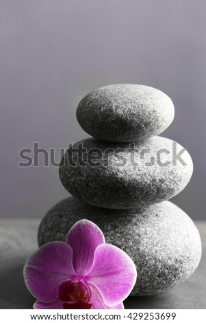 Composition of spa pebbles with orchid flower on grey background