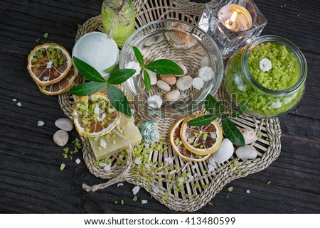 Composition of spa treatment with green salt and soap on wooden background. Spa concept. - stock photo