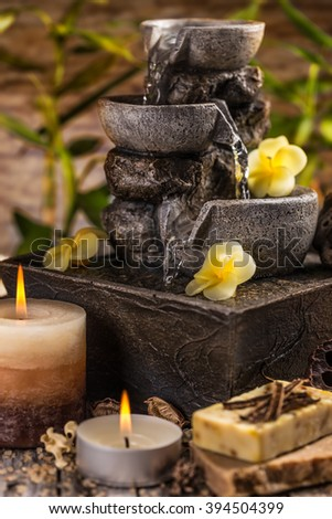 Composition of spa treatment with pouring water fountain - stock photo