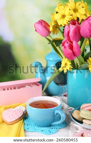 Composition of spring flowers, tea and cookies on table on natural background - stock photo