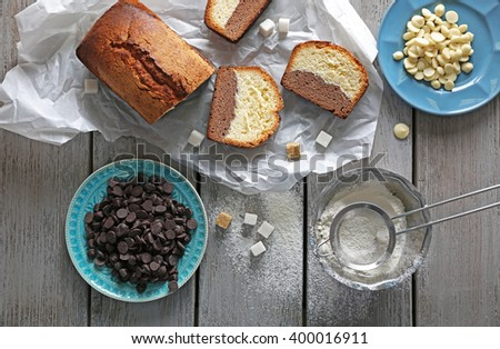 Composition of tasty cake with chocolate morsels and sugar on grey wooden table background, top view - stock photo
