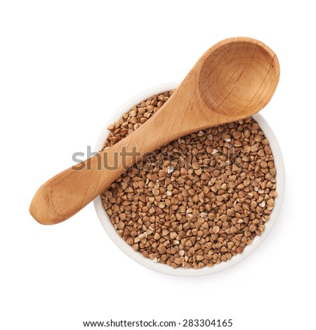 Composition of the white ceramic bowl full of the buckwheat seeds and wooden spoon,  isolated over the white background - stock photo