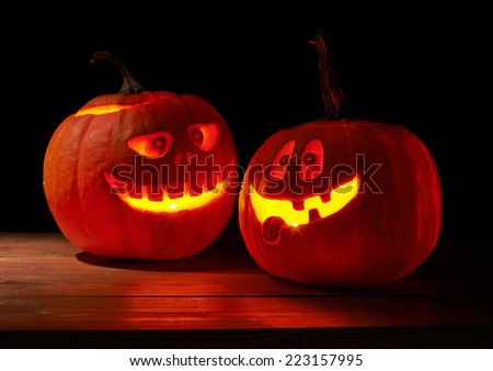 Composition of two glowing from the inside jack o lantern Halloween pumpkins, composition in a low key dramatic lighting - stock photo