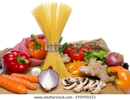 Composition of uncooked spaghetti and different types of vegetables, isolated on white