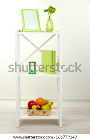 Composition of various home furnishing on white shelf on grey wall background - stock photo