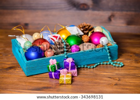 composition of vintage wooden box with Christmas decoration, tinsel,  pinecones, stars, balls and gifts on wooden background, closeup - stock photo