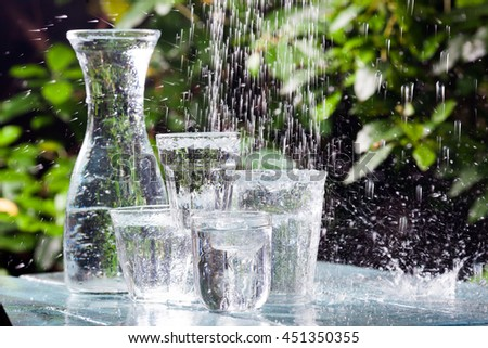 Composition of water glasses in the rain. - stock photo