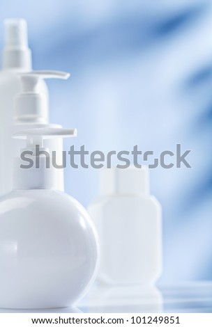 composition of white skincare items on blue background - stock photo