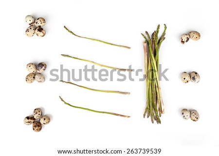 Composition of wild asparagus and quail eggs on white background, above view. - stock photo