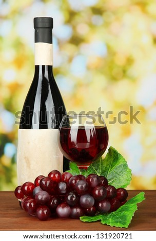 Composition of wine bottle, glass and  grape, on bright background