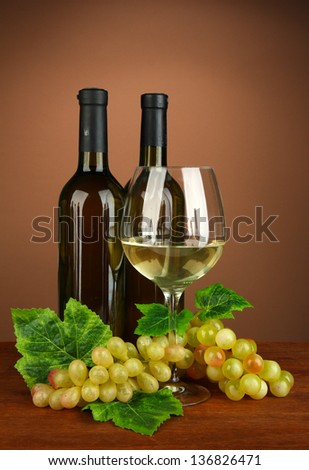 Composition of wine bottles, glass of white wine, grape on color background