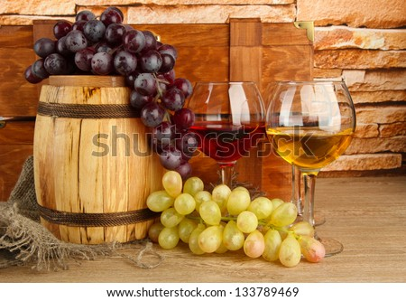 composition of wine,box and grapes on wooden barrel on table on brick wall background - stock photo