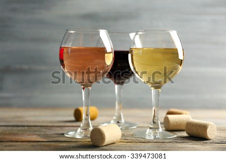 Composition of wine glasses and corks on wooden table against grey background - stock photo