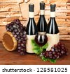 Composition of wine, wooden barrel and  grape, on stone background - stock photo