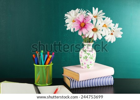 Composition on desk with books and flowers on green blackboard background - stock photo